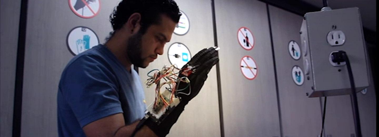 Adrián Chamorro, estudiante de Ingeniería Física de la U.N.         Sede Medellín, creó un sistema habilitado para interpretar diez         palabras de la lengua de señas colombiana, que funciona mediante         un guante de tela convencional con recubrimiento de caucho que         fue reformado (Foto: captura de pantalla Unimedios)